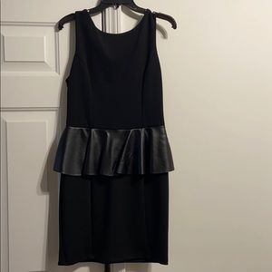Black bodycon dress with leather embellishment.